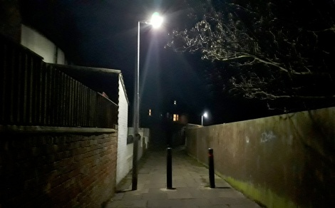 Entrance to the Cuttleby passageway, receding into back walls, lit by a single streetlight in the foreground