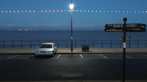 View from Cleethorpes central promenade, looking across the sea road out into the estuary at dusk with the tide in. Christmas lights border the top of the shot.