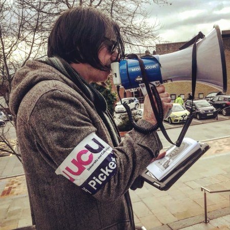 Side view of me reading poetry through a megaphone, wearing a picket armband