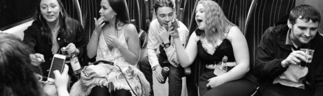 Passengers on a local train drinking booze, presumably en route to a night on the town