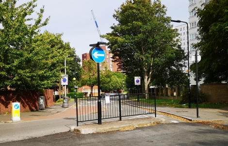 The barrier is a metal railing in the foreground; beyond it stand trees and high-rise tower blocks